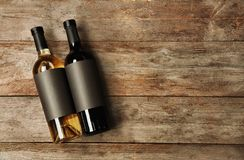 Flaskor med tomma etiketter på träbakgrund Arkivbilder