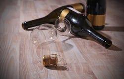 Flaskor med vin och tomt vinexponeringsglas arkivfoto