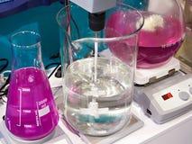Flaskor och blandareshaker i kemiskt laboratorium Fotografering för Bildbyråer