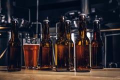 Flaskor och exponeringsglas av hantverköl på trästång kontrar på det indie bryggeriet arkivbild