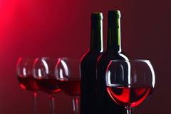 Flaskor och exponeringsglas av rött vin Arkivfoto