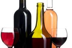 Flaskor och exponeringsglas med vin som isoleras på vit Arkivfoto