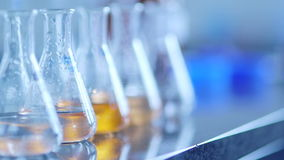 Flasks with chemical in laboratory. Panning shot of flasks with chemical on table in laboratory. Rack focus on containers arranged in a row. Cropped hands of stock footage