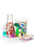 Flasks full of drugs and other medicine. Many different drugs in color pills, tablets in packages and syringe put in laboratory bottles and flasks royalty free stock image