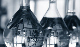 Flasks in laboratory. Volumetric flasks in medical laboratory. The first one has the lab image reflected upside down (a computer and some specific measurement Stock Photos
