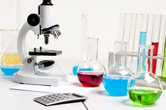 Flasks, microscope, calculator, workplace. Workplace employee lab,flasks with colored liquids, laboratory items Royalty Free Stock Photos