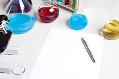 Flasks, pen, blank paper, workplace. Workplace employee lab,flasks with colored liquids, laboratory items Royalty Free Stock Photos