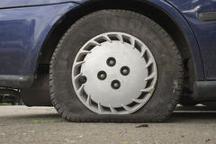 Flat aged tire Royalty Free Stock Photography