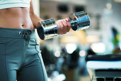 Flat belly due to training. Woman (torso with beautiful belly) working out with dumb-bells Stock Photos