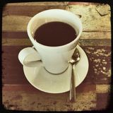 Flat black. A straight Hipstamatic shot of a cup of black coffee on a wooden table Stock Images