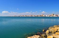 A Flat Blue Sea And Waters Edge Buildings Stock Image