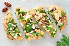 Flat bread with apples, arugula, above view on white marble Royalty Free Stock Photos