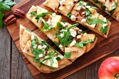 Flat bread with apples, arugula, close up scene over wood Stock Image