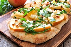 Flat bread with apples, arugula, close up on wood server Royalty Free Stock Image