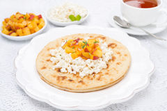 Flat bread with cottage cheese with honey, nuts, fresh peaches Stock Photo