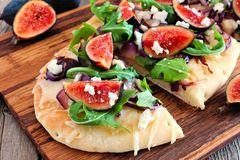 Flat bread with figs, caramelized onions, arugula and cheese, close up. Autumn flat bread pizza with figs, caramelized onions, arugula and cheese, close up on Royalty Free Stock Photo