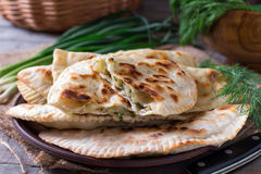 Flat bread with herbs, kutaby, traditional Azerbaijani dish on a plate. On a wooden background Royalty Free Stock Photo