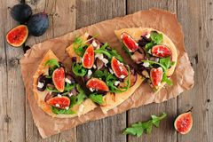 Flat bread pizza with figs, arugula, overhead on rustic wood Royalty Free Stock Images