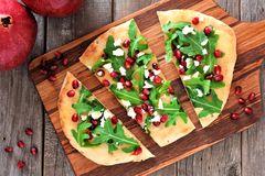 Flat bread with pomegranates, arugula, and cheese, overhead scene Royalty Free Stock Images