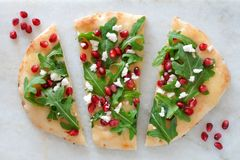 Flat bread with pomegranates, arugula, and cheese on white marble Royalty Free Stock Photos