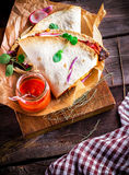 Flat cake with meat and vegetables and sauce in glass on cutting board Royalty Free Stock Photos