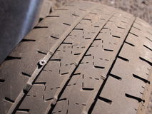 Flat car tire with a silver Philips head screw pierced through the threaded area Royalty Free Stock Photography