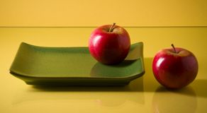Flat ceramic plate and two red apples on yellow Royalty Free Stock Photography