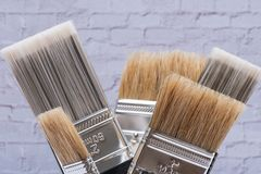 Flat Chip and Flat Cut Utility Paint Brushes   on brick wall royalty free stock photos