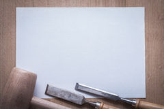 Flat chisels wooden mallet and clean sheet of paper on wood boar. D copyspace construction concept Royalty Free Stock Photo