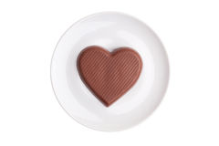 Flat chocolate heart on a saucer on a white backgr Royalty Free Stock Image