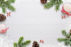 Flat Christmas background scene with fir branches, bows, candles, pinecones and snowflakes Free space for copy text on white board. Top view Royalty Free Stock Image