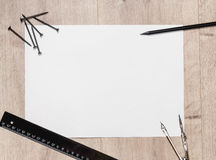 Flat composition of empty drawing sheet and screws, a ruler,  pencil,  compass on wooden table. Workspace repairman with Stock Image