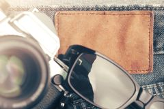 flat composition of vintage SLR camera and sunglasses on worn jeans around blank leather plate - travel and blogger concept royalty free stock image