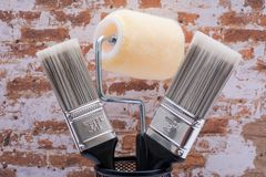 Flat Cut Utility Paint Brushes and High Density Knit Fabric Trim Roller with Frame  on brick wall. Background stock photography