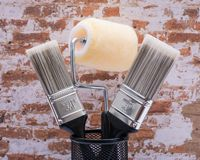 Flat Cut Utility Paint Brushes and High Density Knit Fabric Trim Roller with Frame  on brick wall royalty free stock image