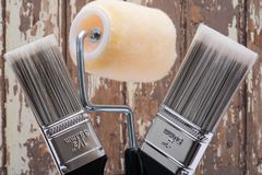 Flat Cut Utility Paint Brushes and High Density Knit Fabric Trim Roller with Frame  on wood. En background royalty free stock images