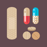 Flat design set of medical & health care design concept. Capsule pills, tablets and medical bandage isolated on dark background Royalty Free Stock Image