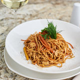 Flat egg noodles with vegetables. Served in big white ceramic round plate with glass of white wine on marble table Royalty Free Stock Image