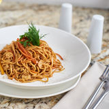 Flat egg noodles with vegetables. Served in big white ceramic round plate with glass of white wine on marble table Stock Photos