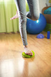 Flat feet correction exercise. Girl walking over spiked half balance massage balls Royalty Free Stock Images