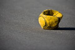 Flat football on the street. Yellow football with lost air on the street Stock Photo