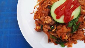 Flat fried noodles. Hot and spicy fried flat noodles or kuey tiaw on white plate and used rough blue table royalty free stock images