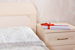 Flat gift box with red bow. Lying on the nightstand next to the bed Stock Image