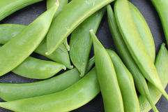 Flat Green Beans Closeup. Closeup image of a fresh pile of Flat Green Beans on a dark background Royalty Free Stock Images