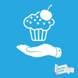 Flat hand presenting white cake icon with cherry on a blue backg Royalty Free Stock Photography