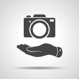 Flat hand shows the photo camera icon Royalty Free Stock Photos