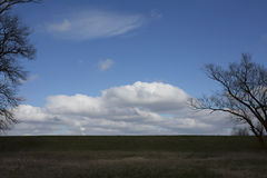 Flat horizon. Horizontal country landscape with sky, big clouds, grass and trees. Stock Photos