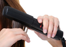 Flat iron applying on female brunette hair Royalty Free Stock Photography