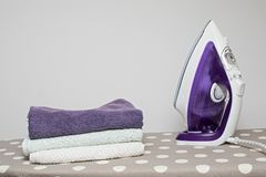 Flat iron and clean clothes on the board royalty free stock photos