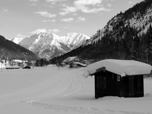 Winter landscape with houses and mountains in black and white. Flat land with cottage full of snow with mountains in the Background in black and White,, farm in royalty free stock photo